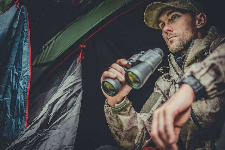 Man Holding Binoculars While Sitting In Tent