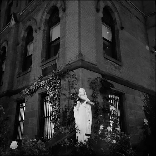 Low Angle View Of Virgin Mary Statue Against Building At Night