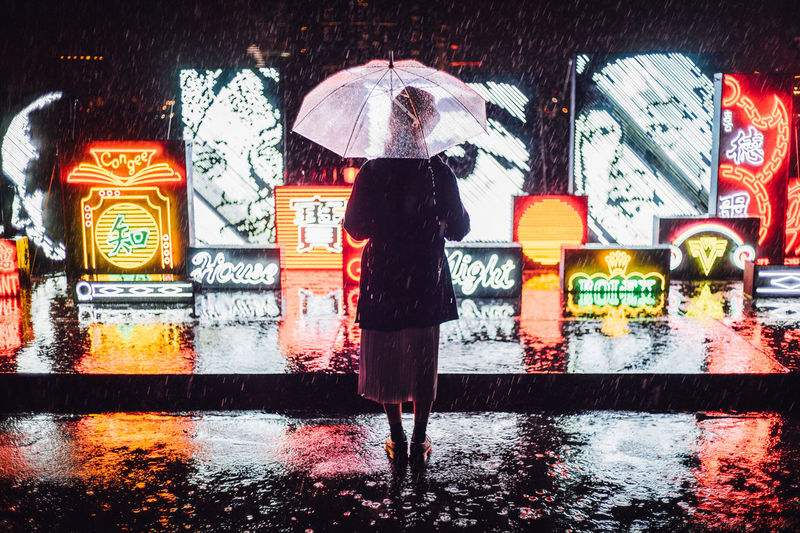 Rear view of woman standing on wet illuminated during rainy season