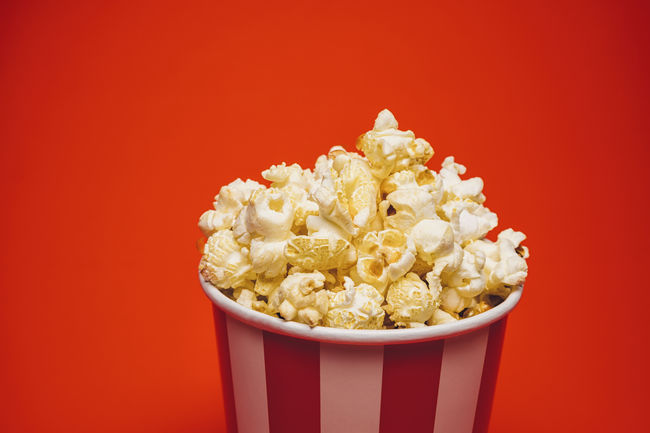 Fresh Popcorn in a round box and around on a bright red background Beverage Box Copy Space Hollywood Kettle Popcorn Red Salt Snack Sugar Background Bowl Butter Carbohydrates Cinema Corn Crunchy Delicious Eat Entertainment Food Movıe Striped Sweet Food Tasty