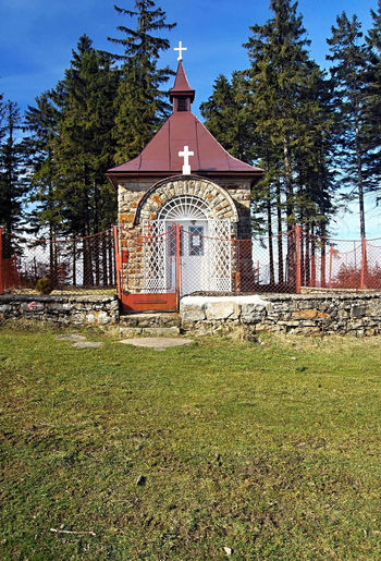 stone chapel on Murinkovy vrch hill on czech - slovakian borders in Moravskoslezske Beskydy mountains with trees on the background and clear sky Chapel Clear Sky Czech Republic Grass Horni Lomna Moravskoslezske Beskydy Murinkovy Vrch Slovakia Architecture Built Structure Outdoors Place Of Worship Religion Tree