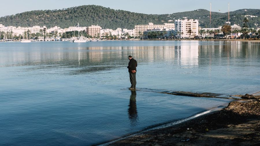 Man standing at riverbank against sky