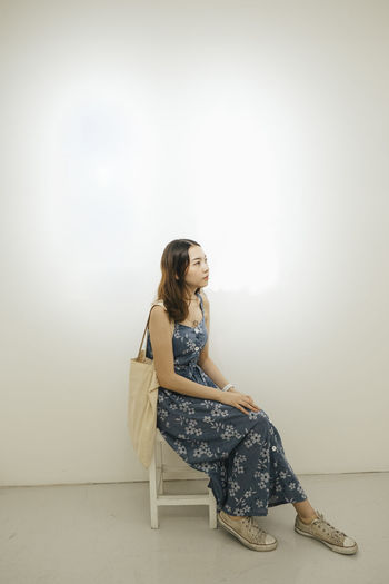 Woman sitting on seat against wall at home
