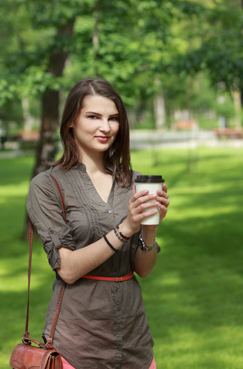 Woman with a coffee cup in an urban park One Person Young Adult Holding Front View Real People Focus On Foreground Leisure Activity Three Quarter Length Casual Clothing Lifestyles Adult Beautiful Woman Outdoors Woman Young Woman Coffee Cup Coffee Mug Coffee Portrait Portrait Of A Woman Urban Park Park - Man Made Space