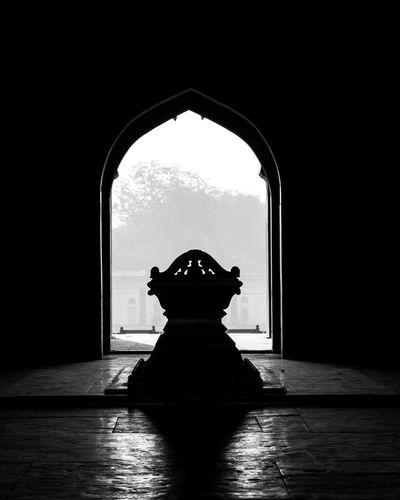 Silhouette of a tomb on floor against sky seen through door