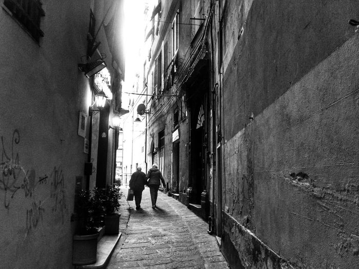 Genova Centro Storico Di Genova Caroggi Vicoligenova Walking The Way Forward Real People Built Structure Lifestyles Architecture Men Sunlight Day Full Length Outdoors Two People Building Exterior Sky Adult People