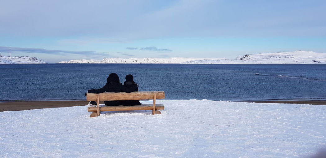Rear View Of Friends Sitting On Bench By Lake Against Sky During Winter