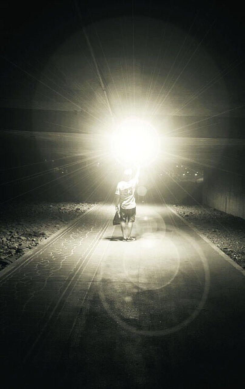MAN IN TUNNEL AT NIGHT