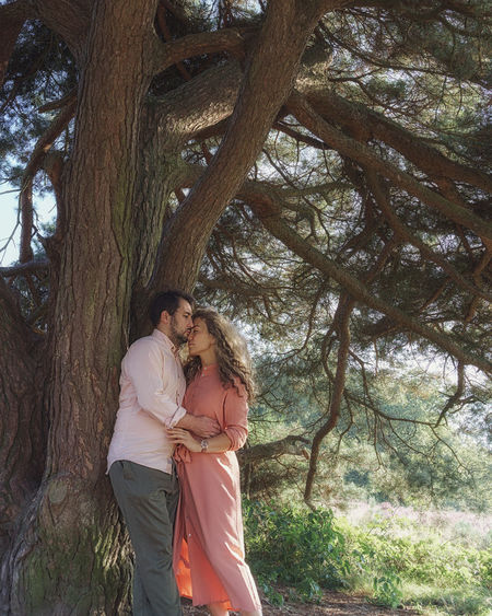 Rear view of couple standing against trees