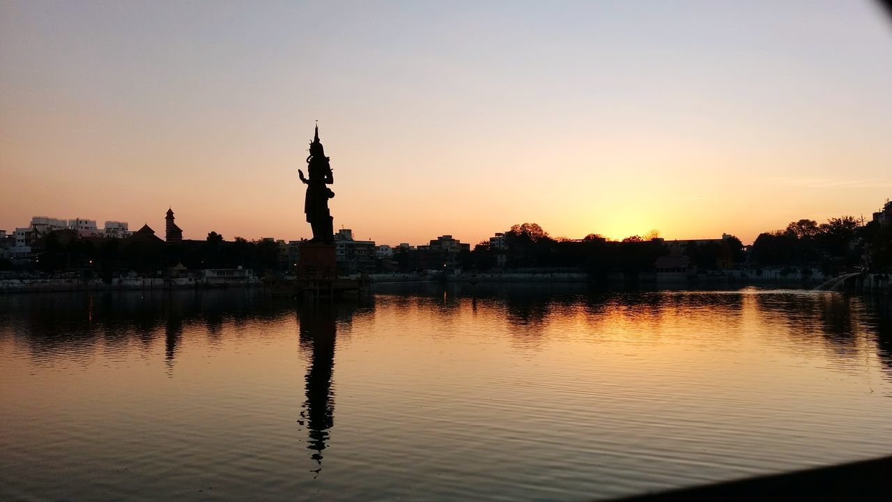 sunset, silhouette, reflection, statue, travel destinations, water, sculpture, waterfront, human representation, sky, outdoors, built structure, architecture, lake, building exterior, nature, no people, city, beauty in nature, tree, day