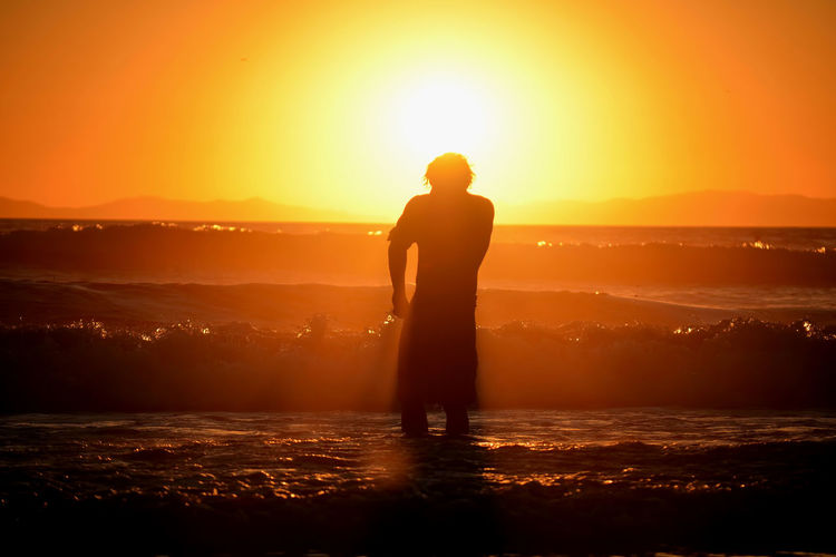 Silhouette man standing by sea against sky during sunset