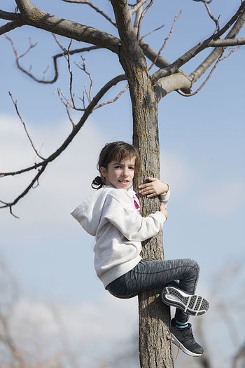 Ten-year-old girl climbing on a tree looking at the camera. Horizontal shot with natural light 10 Years Bare Tree Branch Casual Clothing Childhood Day Girl Happiness Leisure Activity Lifestyles Looking At Camera Low Angle View Nature One Person Outdoors People People Photography Portrait Real People Rope Swing Sky Smiling Standing Tree Tree Trunk