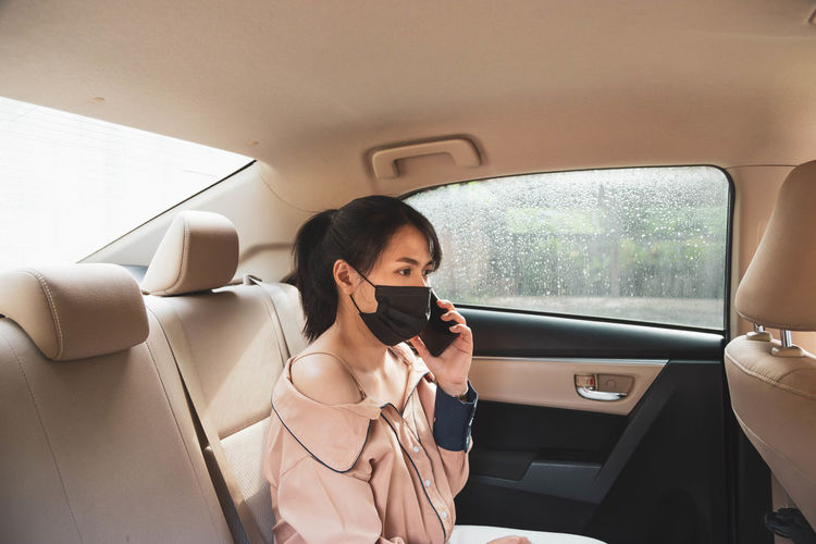 Side view of woman wearing mask talking on phone while sitting in car