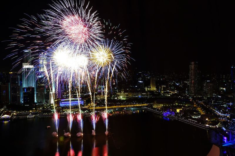 Firework display over river and buildings at night