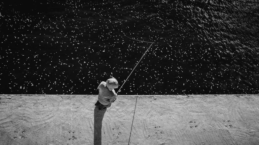 Rear view of a man fishing at night