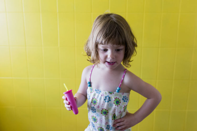 Cute girl holding toy against yellow wall
