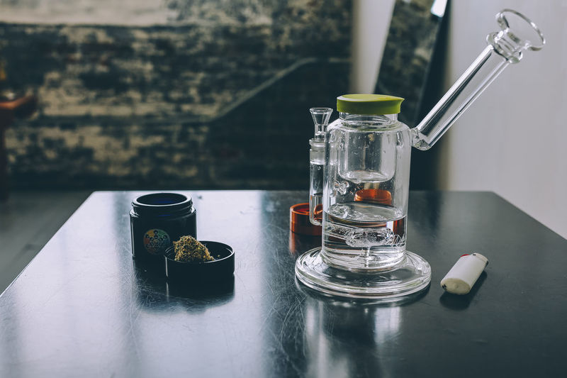 Close-up of water bong and marijuana on table