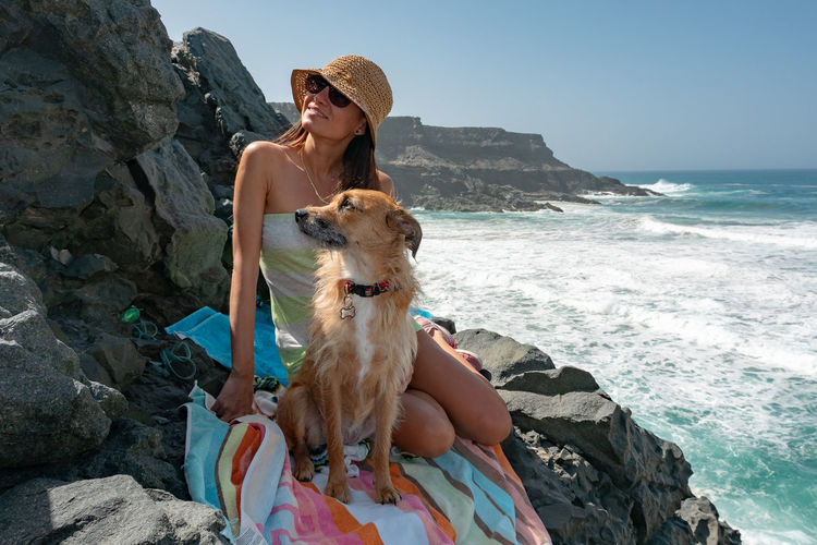 Rock Sea Water Rock - Object One Animal Solid One Person Leisure Activity Real People Beach Land Canine Mammal Nature Pets Dog Lifestyles Sitting Outdoors