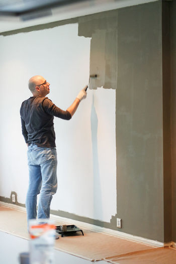 Man standing against wall at home