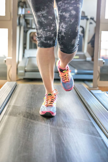 Close up of woman legs in colorful shoes running on treadmill machine in gym. Fast training indoor. Healthy active lifestyle concept. Woman Gym Exercising Females Girl Running Bicips Tapis Roulant Athlete Sport Press Machine Training Trainer Triceps Legs Lifestyles Healthy Biceps Muscles Indoors  Low Section One Person Human Leg Shoe Real People Indoors  Body Part Human Body Part Women Leisure Activity Day Motion Healthy Lifestyle Sports Shoe Child Adult Human Limb Shorts
