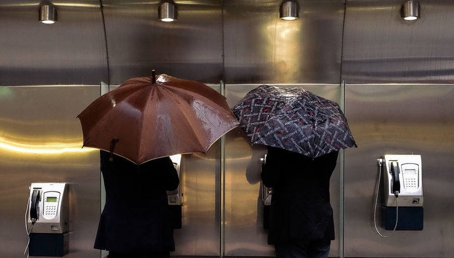 Rear view of people holding umbrella