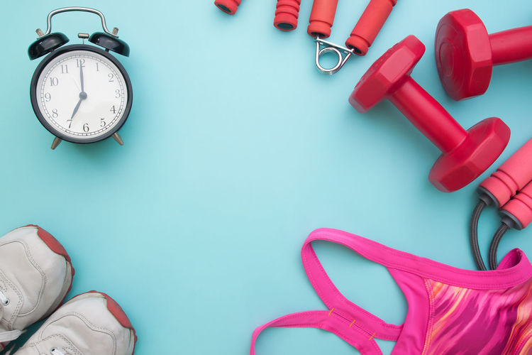 Directly above shot of alarm clock with sports equipment on blue background