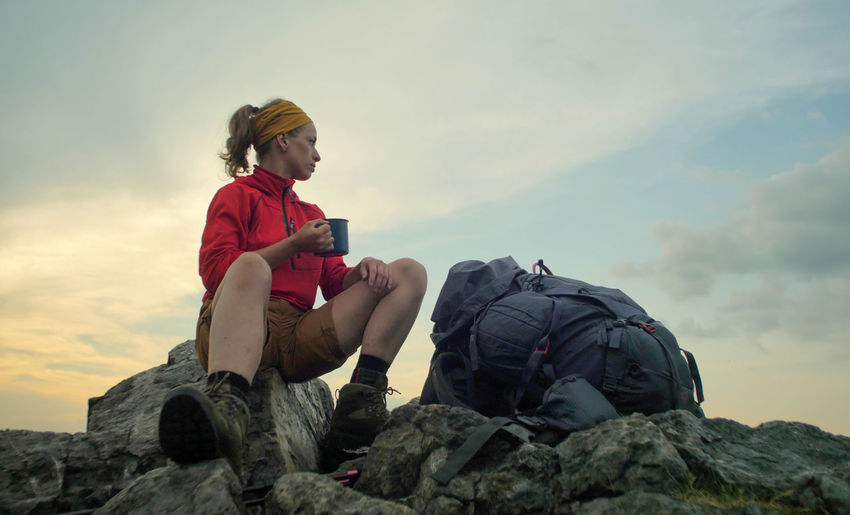 caucasian female hiker sitting on a rocky peak next to a backpack drinking beverage out of a mug Alpine Backpacking Boots Camping Expedition Freedom Hiking Nature Sitting Travel Trekking Woman Active Activity Adventure Backpack Child Cloud - Sky Female Full Length Hobby Holding Leisure Activity Lifestyles Mountain Nature One Person Outdoors Peak People person Real People Rock Rock - Object Sitting Sky Solid Technology Trek