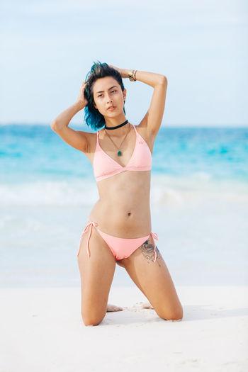 Woman In Bikini Kneeling On Sand At Beach Against Sky