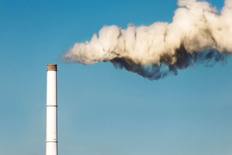 Smoke emitting from chimney against blue sky