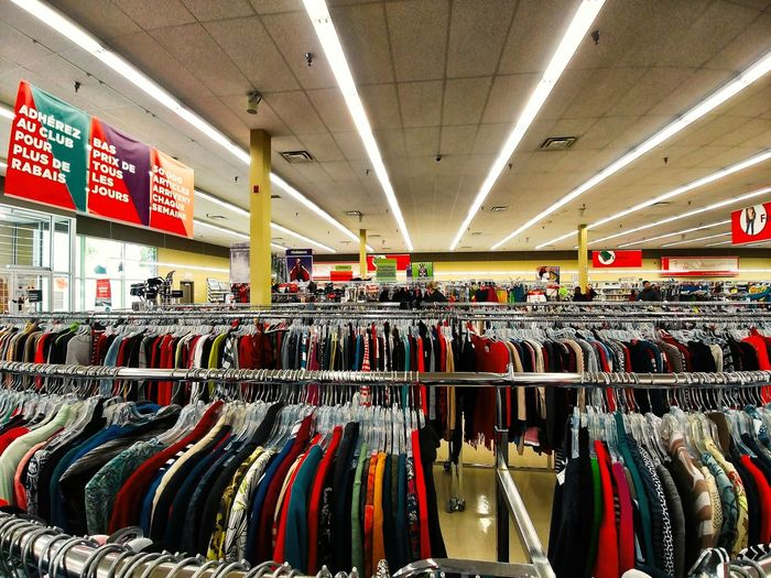 Indoors  Retail  Store In A Row Shopping Large Group Of Objects Choice Illuminated Clothing Coathanger Rack Variation Hanging Abundance No People Clothing Store Text Arrangement Multi Colored Sale Consumerism Retail Display Order Ceiling Boutique