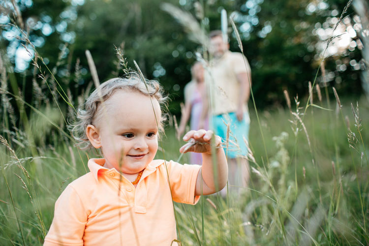 A happy little child touching grass stems. A portrait of a smiling toddler boy exploring nature and his parents watching him. Copy Space Discover Your City Exploring Grass Happy Horizontal Nature Touch Blond Hair Boy Child Childhood Curly Hair Enjoy Excitement Kid Nature_collection Outdoor Outdoors Parents Real People Relax Summer Toddler  Touching