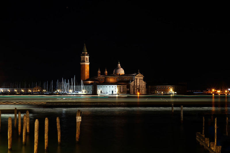 Light Trails Over Grand Canal By Church Of San Giorgio Maggiore Against Sky At Night