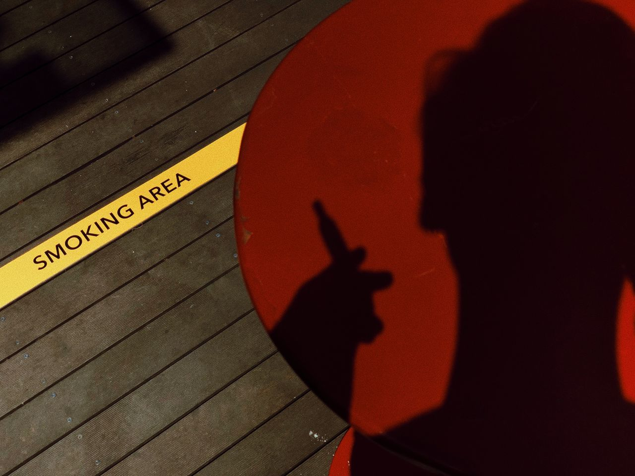 text, communication, western script, sign, high angle view, shadow, indoors, close-up, real people, one person, day, red, capital letter, wood - material, information, table, orange color, yellow