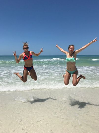 Full length of friends jumping at beach against clear sky