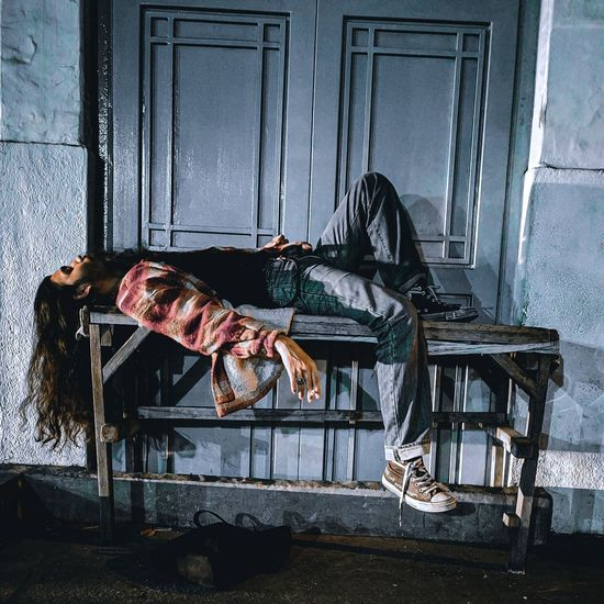 Full length of man lying down on table by door