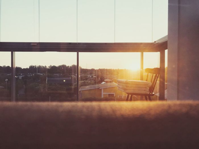 Empty chairs and table against sky seen through glass window