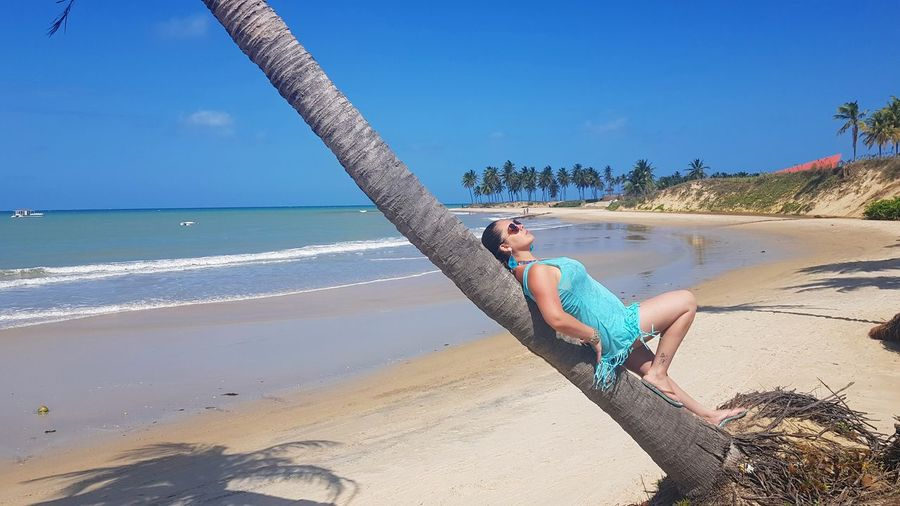 Woman relaxing on beach against blue sky