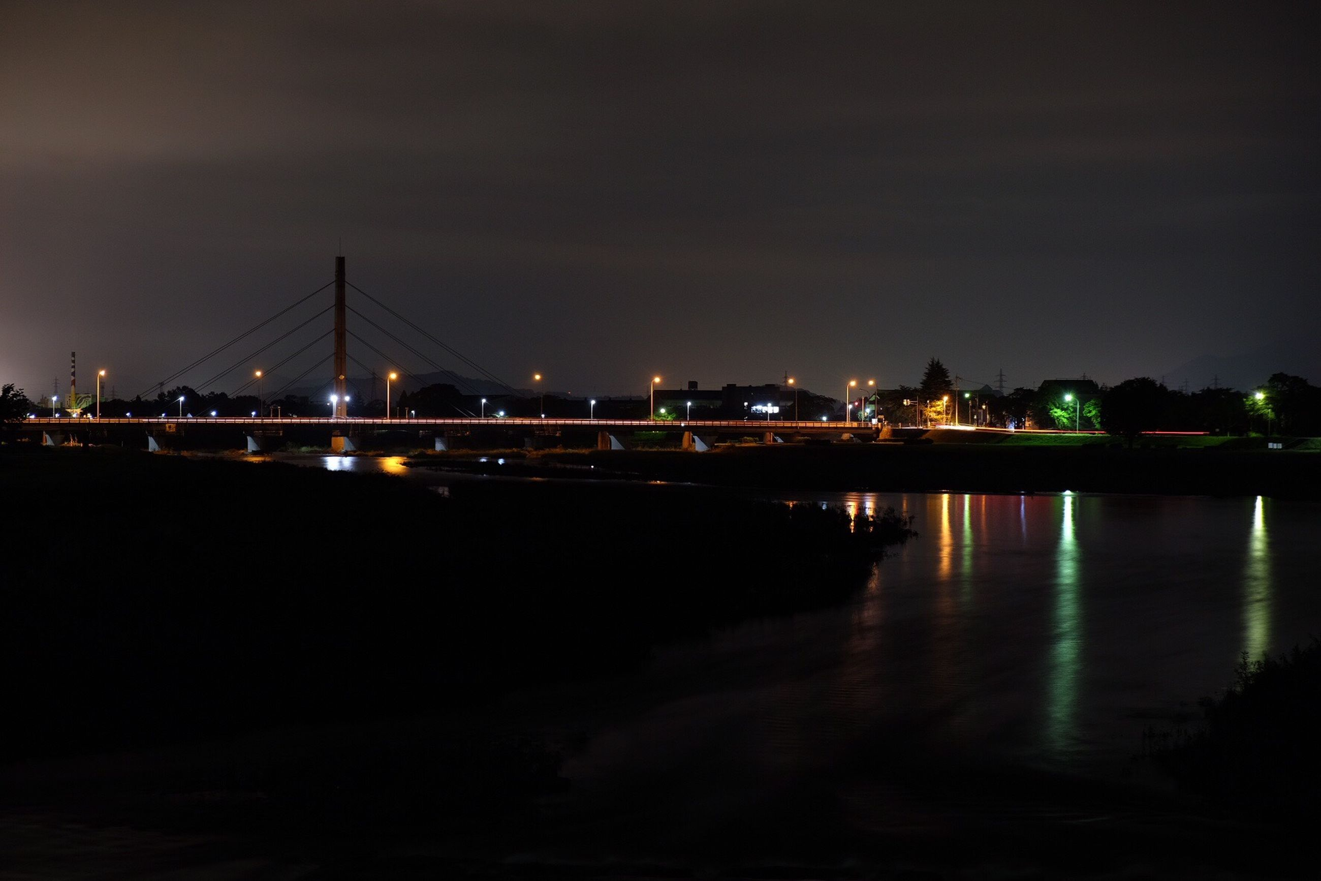 water, illuminated, connection, bridge - man made structure, suspension bridge, architecture, built structure, reflection, engineering, transportation, dark, travel destinations, night, river, cable-stayed bridge, waterfront, tourism, sky, sea, tranquility, bridge, outdoors, tranquil scene, famous place, scenics, city life