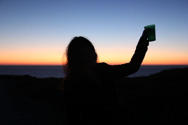 Silhouette Woman Raising Toast Against Blue Sky During Sunset