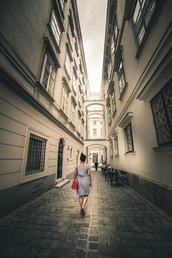 Rear View Of Woman Walking On Footpath Amidst Buildings