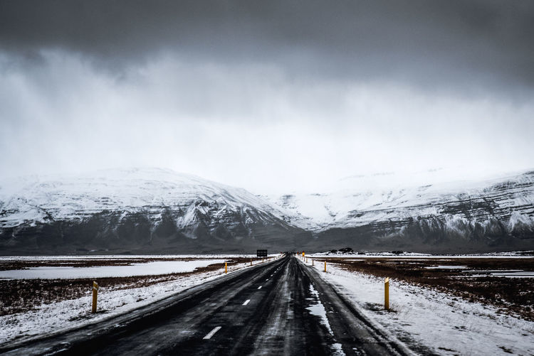 Road leading towards snow covered mountain against sky