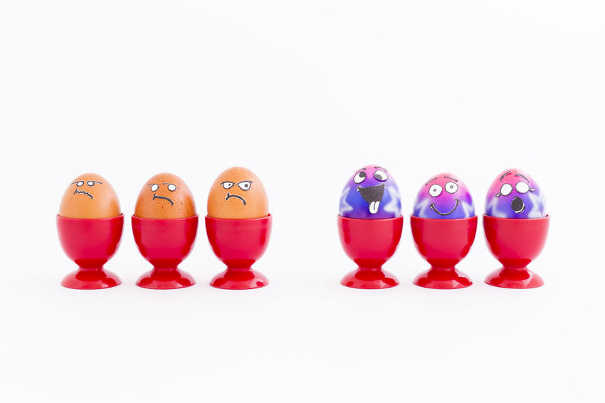 Group of colorful painted Easter eggs with funny cartoon style faces and group of grumpy looking brown eggs in red plastic egg cups on white background Celebration Easter Easter Eggs Egg Cups Grumpy Happy Brown Cartoon Cheerful Close-up Contrast Copy Space Cups Discrimination Eggs Faces In A Row Jealous Multi Colored No People Party Plastic Red Spring Time White Background