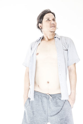 Thoughtful Man With Hands In Pockets Standing Against White Background