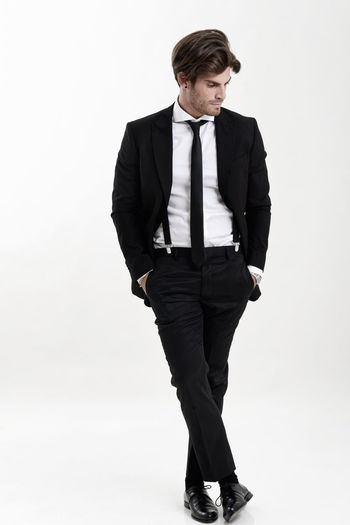 Man wearing suit standing with hands in pockets against white background