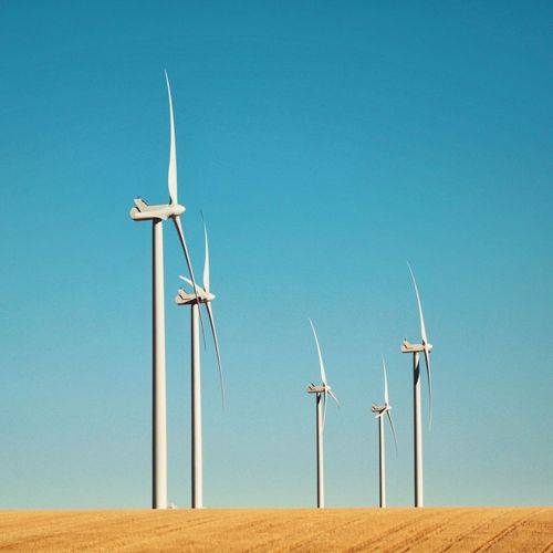 Low angle view of windmills on field against clear blue sky