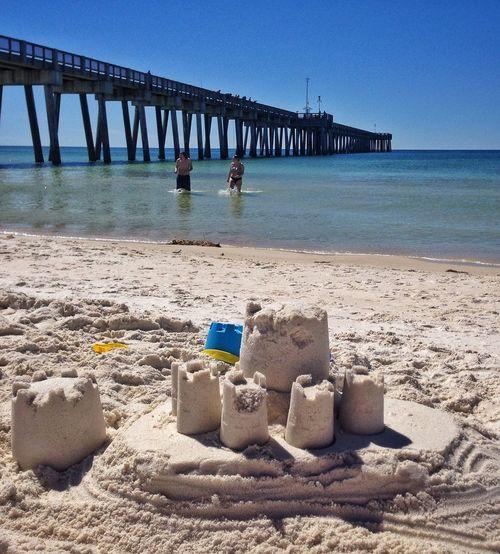 Sandcastle At Beach Against Clear Blue Sky