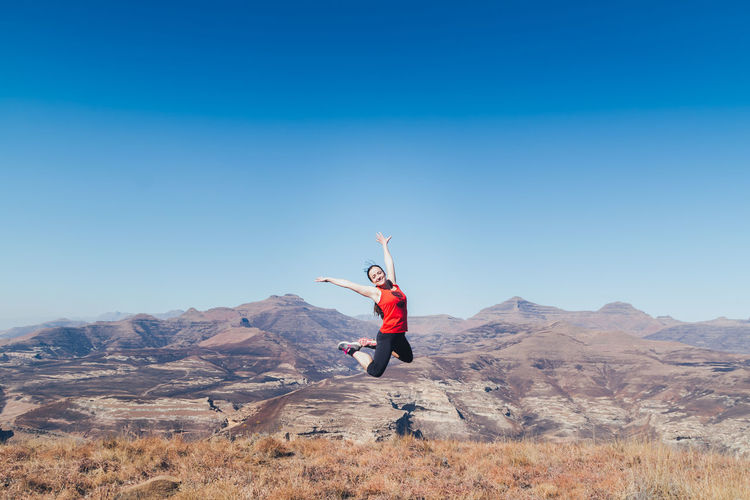 Happy Woman With Arms Raised Jumping On Mountain Against Clear Sky