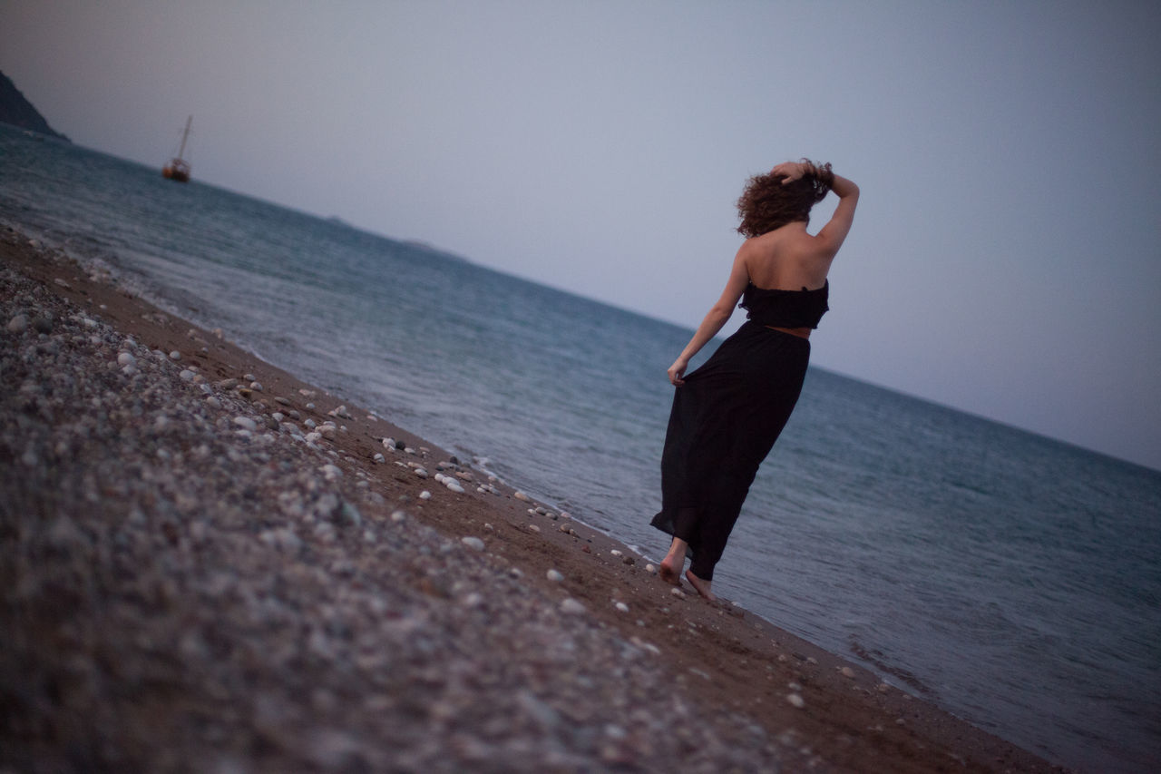Rear View Of Woman With Hand In Hair Looking At Beach