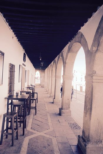 Through the Colonnades Al Fresco Alley Arch Arches Architecture Built Structure Chair Day Indoors  No People Street
