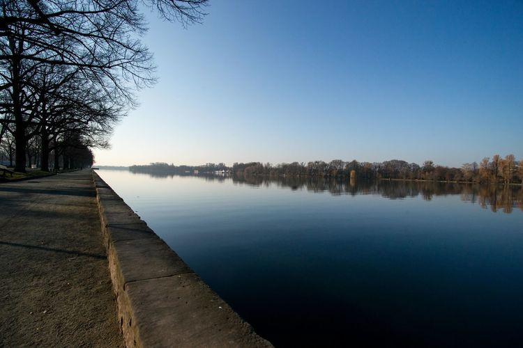 Empty footpath by river against clear blue sky